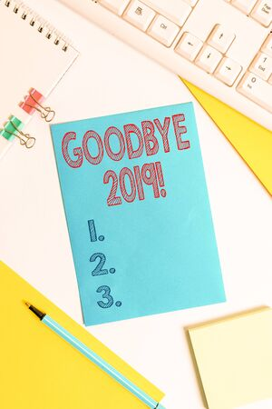 Conceptual hand writing showing Goodbye 2019. Concept meaning express good wishes when parting or at the end of last year Colored paper binder clip sheets white desk empty space Imagens