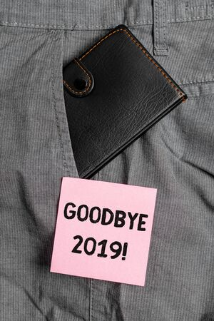 Conceptual hand writing showing Goodbye 2019. Concept meaning express good wishes when parting or at the end of last year Small wallet inside trouser front pocket near notation paper Imagens