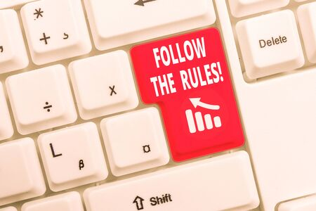 Text sign showing Follow The Rules. Business photo text go with regulations governing conduct or procedure White pc keyboard with empty note paper above white background key copy space