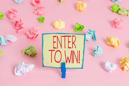 Text sign showing Enter To Win. Business photo text exchanging something value for prize chance winning prize Colored crumpled papers empty reminder pink floor background clothespin Фото со стока