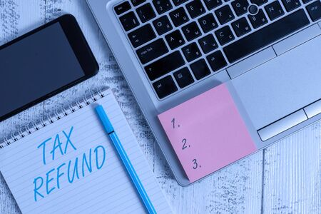 Writing note showing Tax Refund. Business concept for refund on tax when the tax liability is less than the tax paid Laptop ruled notepad smartphone sticky note on wooden table
