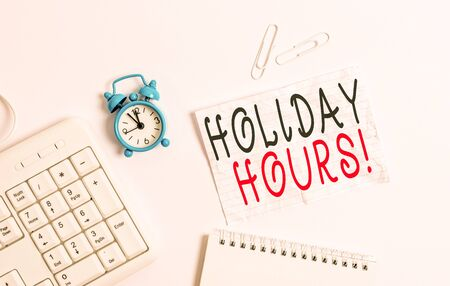Writing note showing Holiday Hours. Business concept for Overtime work on for employees under flexible work schedules Blank paper with copy space on the table with clock and pc keyboard