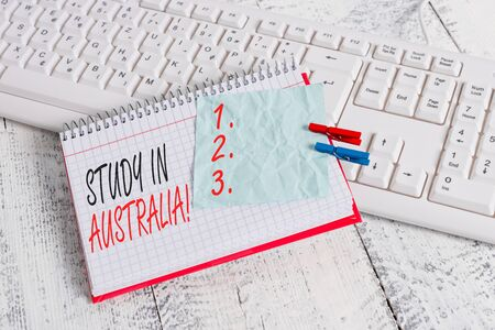 Text sign showing Study In Australia. Business photo showcasing going into foreign country order complete your studies notebook paper reminder clothespin pinned sheet white keyboard light wooden