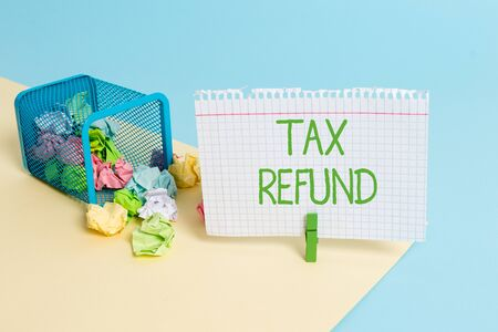 Text sign showing Tax Refund. Business photo text refund on tax when the tax liability is less than the tax paid Trash bin crumpled paper clothespin empty reminder office supplies tipped