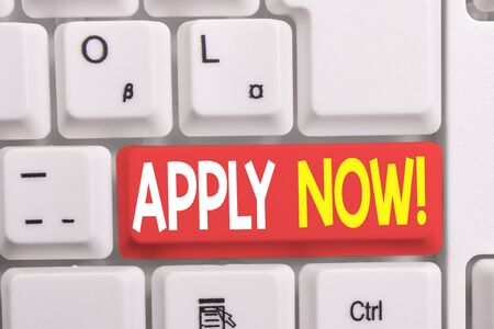Writing note showing Apply Now. Business concept for request something officially in writing or by sending in form White pc keyboard with note paper above the white background