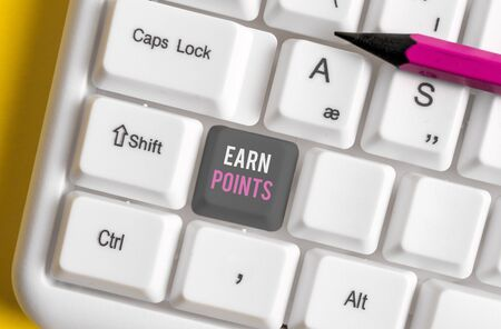 Writing note showing Earn Points. Business concept for getting praise or approval for something you have done White pc keyboard with note paper above the white background