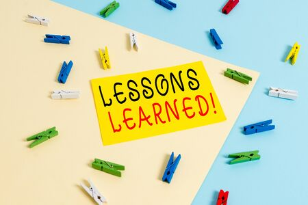 Text sign showing Lessons Learned. Business photo text experiences distilled project that should actively taken Colored clothespin paper empty reminder yellow blue floor background office 写真素材