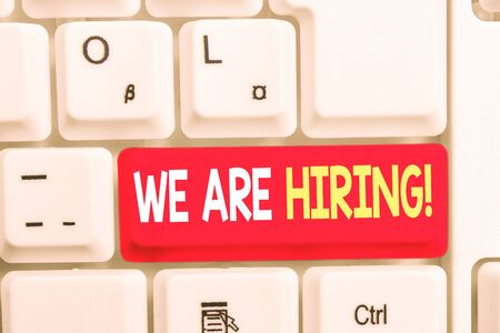 Writing note showing We Are Hiring. Business concept for recently you employ someone or pay someone to do particular job White pc keyboard with note paper above the white background 写真素材