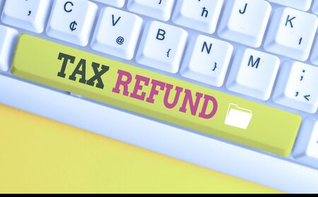 Text sign showing Tax Refund. Business photo text refund on tax when the tax liability is less than the tax paid White pc keyboard with empty note paper above white background key copy space Imagens