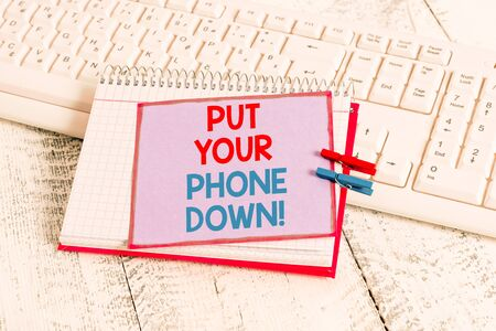 Word writing text Put Your Phone Down. Business photo showcasing end telephone connection saying goodbye caller notebook paper reminder clothespin pinned sheet white keyboard light wooden