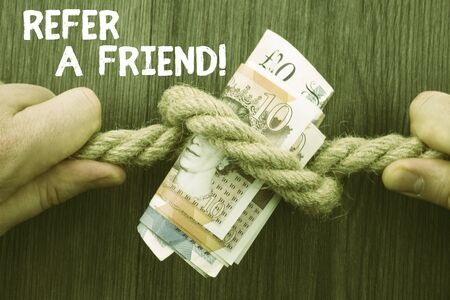 Writing note showing Refer A Friend. Business concept for direct someone to another or send him something like gift Front view wooden background two hands knot rope bills inside symbol