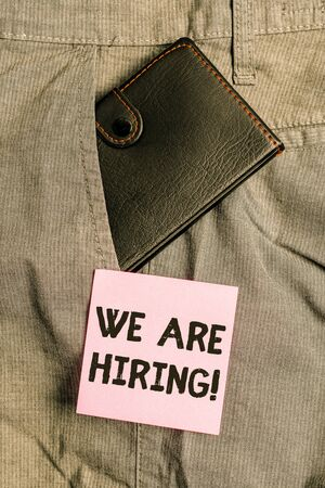 Conceptual hand writing showing We Are Hiring. Concept meaning recently you employ someone or pay someone to do particular job Small wallet inside trouser front pocket near notation paper
