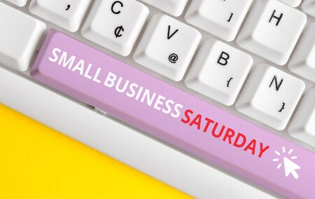 Escribir nota mostrando el sábado de pequeñas empresas. Concepto de negocio para vacaciones de compras americanas celebradas durante el sábado teclado de pc blanco con papel de nota sobre el fondo blanco. Foto de archivo
