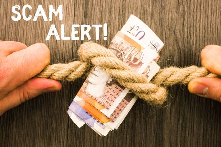 Writing note showing Scam Alert. Business concept for fraudulently obtain money from victim by persuading him Front view wooden background two hands knot rope bills inside symbol