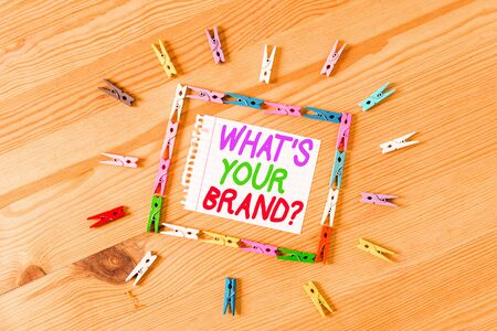 Handwriting text writing What S Your Brand Question. Conceptual photo asking about product logo does or what you communicate Colored clothespin papers empty reminder wooden floor background office