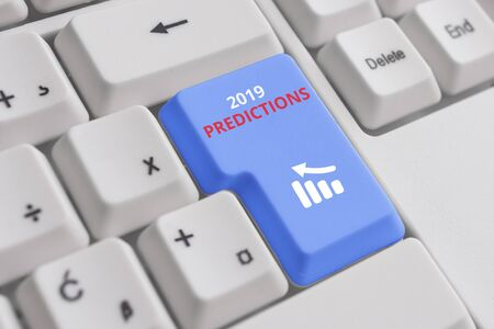 Conceptual hand writing showing 2019 Predictions. Concept meaning statement about what you think will happen in 2019 White pc keyboard with note paper above the white background