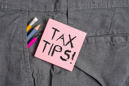 Conceptual hand writing showing Tax Tips. Concept meaning compulsory contribution to state revenue levied by government Writing equipment and pink note paper inside pocket of trousers
