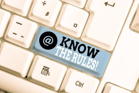 Text sign showing Know The Rules. Business photo showcasing set explicit or regulation principles governing conduct White pc keyboard with empty note paper above white background key copy space Foto de archivo - 130025811