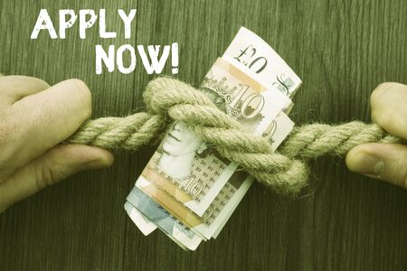 Writing note showing Apply Now. Business concept for request something officially in writing or by sending in form Front view wooden background two hands knot rope bills inside symbol 写真素材