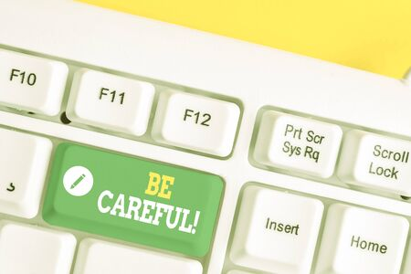 Text sign showing Be Careful. Business photo showcasing making sure of avoiding potential danger mishap or harm White pc keyboard with empty note paper above white background key copy space