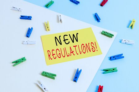 Text sign showing New Regulations. Business photo text rules made government order control something done Colored clothespin paper empty reminder yellow blue floor background office Stock Photo