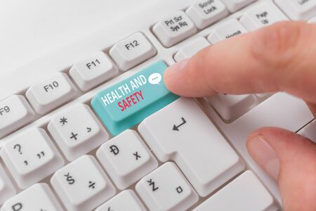 Writing note showing Health And Safety. Business concept for procedures intended to prevent accident in workplace White pc keyboard with note paper above the white background