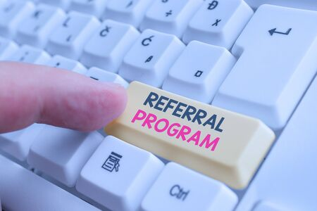 Writing note showing Referral Program. Business concept for employees are rewarded for introducing suitable recruits White pc keyboard with note paper above the white background