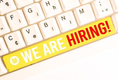 Word writing text We Are Hiring. Business photo showcasing recently you employ someone or pay someone to do particular job White pc keyboard with empty note paper above white background key copy space