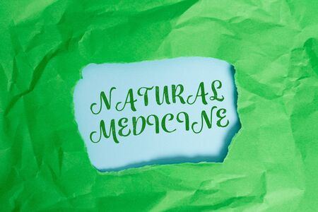Text sign showing Natural Medicine. Business photo text any of various systems of healing or treating disease Green crumpled ripped colored paper sheet centre torn colorful background