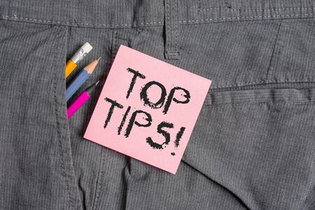 Conceptual hand writing showing Top Tips. Concept meaning small but particularly useful piece of practical advice Writing equipment and pink note paper inside pocket of trousers