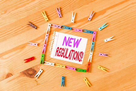 Handwriting text writing New Regulations. Conceptual photo rules made government order control something done Colored clothespin papers empty reminder wooden floor background office Фото со стока - 130027653