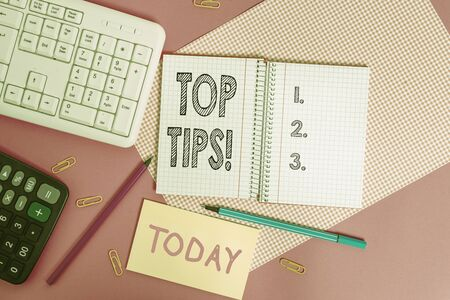 Writing note showing Top Tips. Business concept for small but particularly useful piece of practical advice Writing equipments and computer stuffs placed above colored plain table