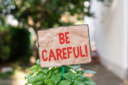 Writing note showing Be Careful. Business concept for making sure of avoiding potential danger mishap or harm Plain paper attached to stick and placed in the grassy land