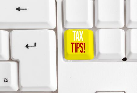Handwriting text writing Tax Tips. Conceptual photo compulsory contribution to state revenue levied by government White pc keyboard with empty note paper above white background key copy space