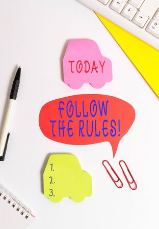 Conceptual hand writing showing Follow The Rules. Concept meaning go with regulations governing conduct or procedure Red bubble copy space paper on the table with clock