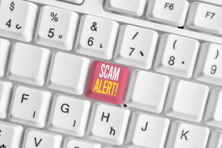 Word writing text Scam Alert. Business photo showcasing fraudulently obtain money from victim by persuading him White pc keyboard with empty note paper above white background key copy space Stockfoto