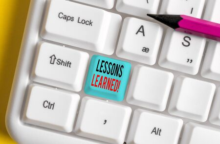 Conceptual hand writing showing Lessons Learned. Concept meaning experiences distilled project that should actively taken White pc keyboard with note paper above the white background