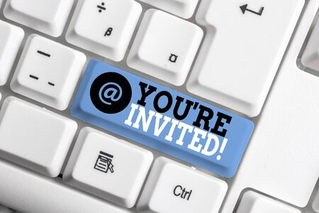Text sign showing You Re Invited. Business photo showcasing make a polite friendly request to someone go somewhere White pc keyboard with empty note paper above white background key copy space Stock Photo