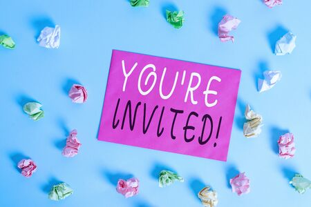 Writing note showing You Re Invited. Business concept for make a polite friendly request to someone go somewhere Colored crumpled rectangle shaped reminder paper light blue background