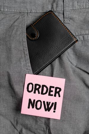 Conceptual hand writing showing Order Now. Concept meaning confirmed request by one party to another to buy sell Small wallet inside trouser front pocket near notation paper Stock Photo