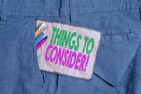 Handwriting text writing Things To Consider. Conceptual photo think about something carefully in order to make decision Writing equipment and brown note paper inside pocket of man work trousers 写真素材