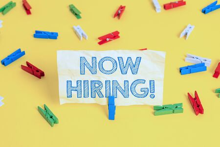 Writing note showing Now Hiring. Business concept for finding evaluating working relationship with future employees Colored clothespin papers empty reminder yellow floor background office