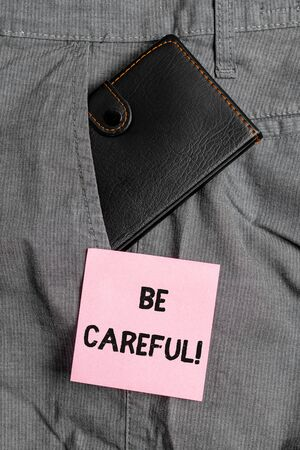 Conceptual hand writing showing Be Careful. Concept meaning making sure of avoiding potential danger mishap or harm Small wallet inside trouser front pocket near notation paper