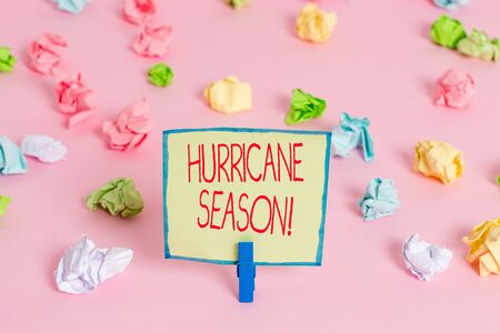 Text sign showing Hurricane Season. Business photo text time when most tropical cyclones are expected to develop Colored crumpled papers empty reminder pink floor background clothespin