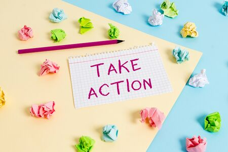 Text sign showing Take Action. Business photo text to do somethingoract in order to get a particular result Colored crumpled papers empty reminder blue yellow background clothespin 写真素材