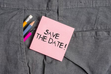 Conceptual hand writing showing Save The Date. Concept meaning remember not schedule anything else on this day Writing equipment and pink note paper inside pocket of trousers