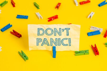 Writing note showing Don T Panic. Business concept for suddenly feel so worried or frightened that you can not behave Colored clothespin papers empty reminder yellow floor background office Stock fotó