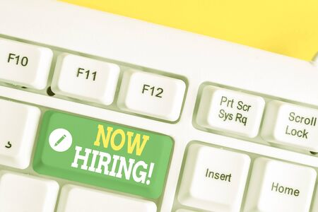 Text sign showing Now Hiring. Business photo showcasing finding evaluating working relationship with future employees White pc keyboard with empty note paper above white background key copy space