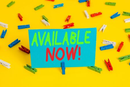 Writing note showing Available Now. Business concept for you can find it obtain or operable at this current moment Colored clothespin papers empty reminder yellow floor background office