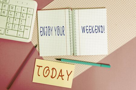 Text sign showing Enjoy Your Weekend. Business photo text wishing someone that something nice will happen at holiday Writing equipments and computer stuffs placed above colored plain table Reklamní fotografie